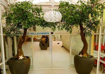 2 geneigte künstliche Bäume (Höhe 400 cm) im Eingang eines Einkaufscenters.