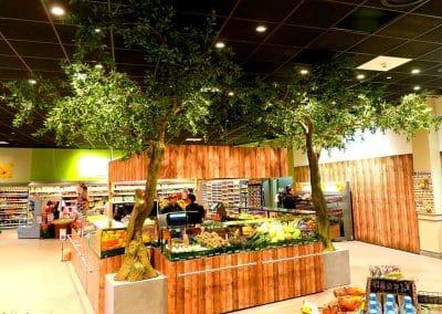 2 geneigte künstliche Olivenbäume im Eingang eines EKZ (Baumhöhe 420 cm inkl. Podest).
