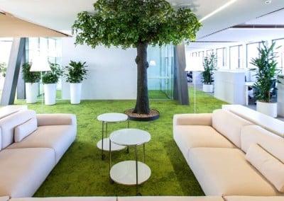 Kunstbaum mit grünen Blättern in Großraumbüro.