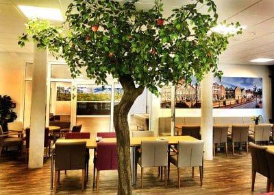 Künstlicher Apfelbaum (300 cm hoch) mit geschwungenem Stamm in einem Seniorenheim.