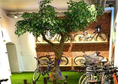 Künstlicher Baum mit gegabeltem Stamm (Höhe 330 cm) in einem Fahrradgeschäft in München.