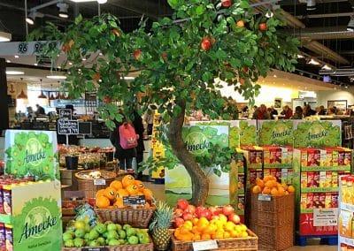 Grün belaubter Deko-Baum (240 cm hoch) mit künstlichen Äpfeln in Werbeaktion.