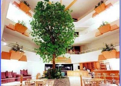 Kunstbaum mit Naturstamm in einem Innenhof.