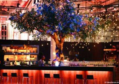 Effektvoll beleuchteter XXL-Kunstbaum (600 cm Baumkrone) von Hadjisky als Bar-Dekoration.