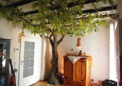 Künstlicher Baum (Eiche) mit Knollenstamm und flacher, lichter Baumkrone in einer Wohnung.