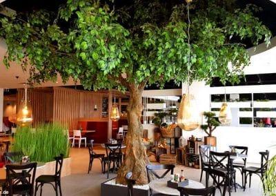 Großer, grün belaubter Kunstbaum ohne Früchte (Ø Baumkrone: 5,00 m; Stammstärke 85 cm) als stimmige Dekoration bei Porta Möbel in Berlin.