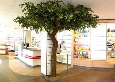 Kunstbaum (Höhe ca. 3,00 m) mit grünem Laub und geschwungenem Stamm (Ø ca. 20 cm) der dekorativ einen massiven Träger kaschiert.