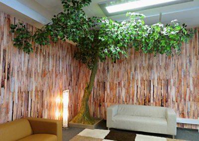 Grün belaubter Kunstbaum, der individuell als Eck-Baum gestaltet wurde.  Höhe ca. 280 cm.