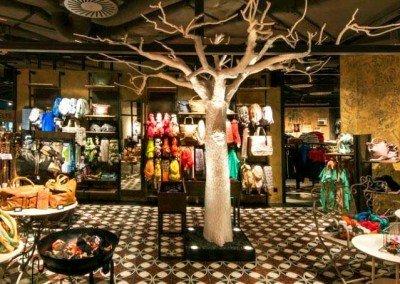 Beleuchteter, kahler Kunstbaum in einer Boutique.