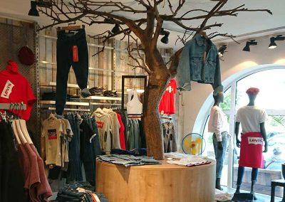 Ein kahler Kunstbaum (Höhe ca. 300 cm) der in einer Boutique stylish mit Bekleidung dekoriert wurde.