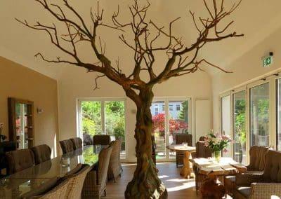 Kahler Kunstbaum ohne Blätter (350 cm Höhe; 360 cm Ø Baumkrone) mit Knollenstamm und dicken Ästen aus Glasfaser als optischer Blickfang.
