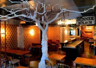 Weißer Kunstbaum ohne Blätter in einem Bistro (mit Löffel-Deko).