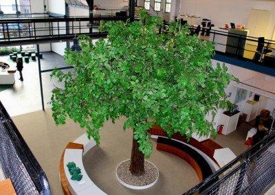 Großer, belaubter Kunstbaum in Großraumbüro.