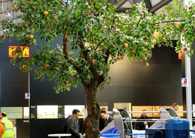 Ein künstlicher Apfelbaum mit Knollenstamm (Höhe ca. 400 cm) als Dekoration auf einem Messestand.