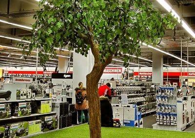 Kunstbaum ohne Früchte (Höhe ca. 320 cm) als Dekoration in einem Elektronikmarkt.