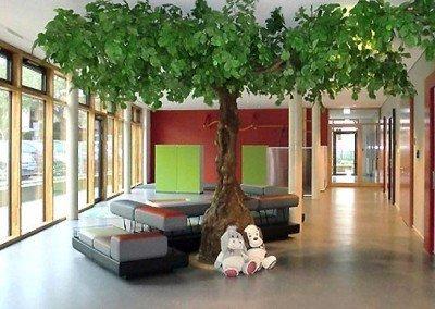 Belaubter Kunstbaum mit breiter Krone in einer Schule.