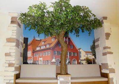 Belaubter Kunstbaum als Dekoration in einer Nische.