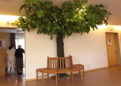 Dicht belaubter Kunstbaum (Linde) in einem Seniorenheim.