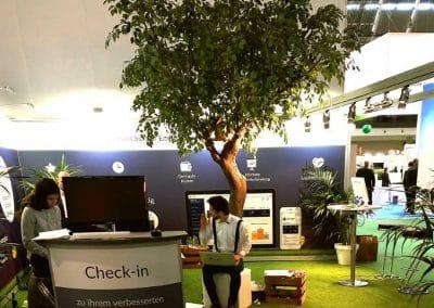 Grün belaubter Kunstbaum (ca. 350 cm hoch) mit geschwungenem Stamm auf einem Messestand in Stuttgart.
