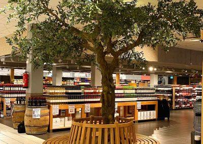 Oliven-Kunstbaum mit Ruhebank in einem Einkaufscenter