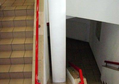 Unverkleidete, runde Deckenstütze in einem Treppenaufgang