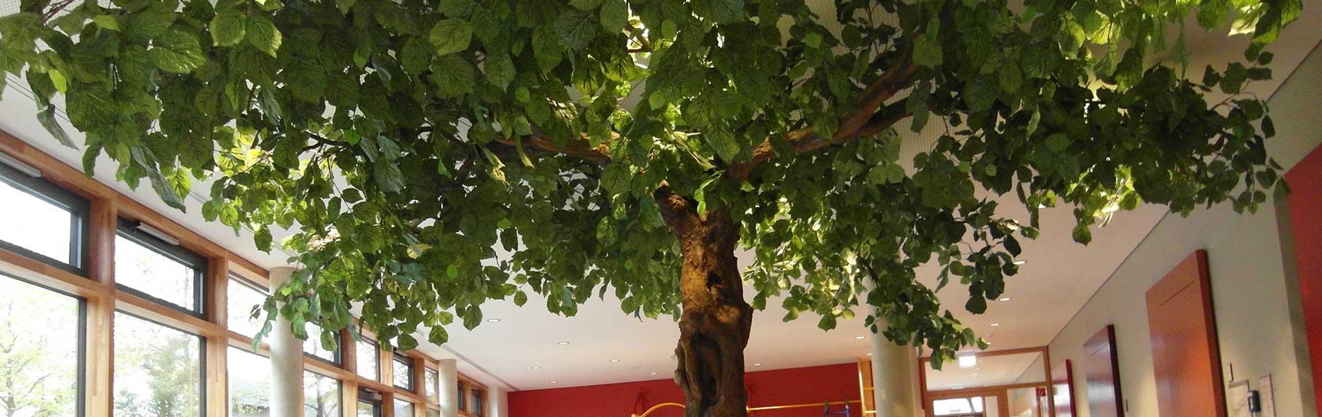 Kunstbaum, grün belaubt mit knorrigem Stamm