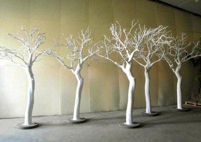 Fünf weiße, kahle Kunstbäume.