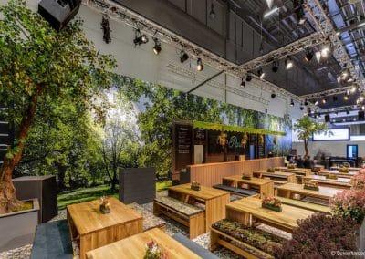 Zwei stark geneigte Kunstbäume als Messedekoration (Höhe ca. 400 cm o. Podest).